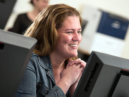 Female sitting in front of computer in class smiling