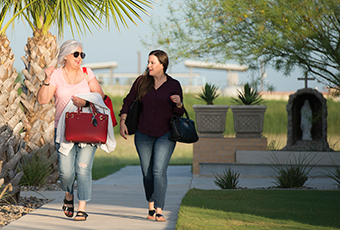 Two females walking by palm trees